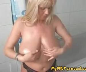 Mature blonde is showing her massive milk jugs to the camera, and playing with them a bit